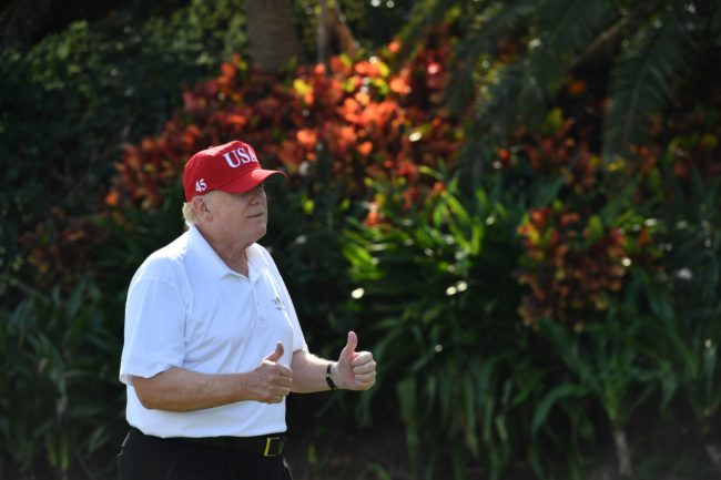 US President Donald Trump holds two thumbs up while meeting with service members of the United States Coast Guard to play golf at Trump International Golf Course in Mar-a-Lago, Florida on December 29, 2017. The President invited members of the Coast Guard to play golf to thank them personally for their service of patrolling the waters near Palm Beach and Mar-a-Lago. / AFP PHOTO / Nicholas Kamm (Photo credit should read NICHOLAS KAMM/AFP/Getty Images)