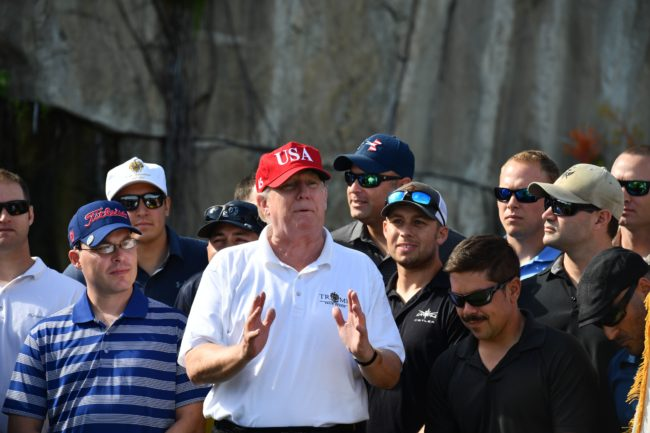US President Donald Trump speaks to service members of the United States Coast Guard during an invitation to play golf at Trump International Golf Course in Mar-a-Lago, Florida on December 29, 2017. The President invited members of the Coast Guard to play golf to thank them personally for their service of patrolling the waters near Palm Beach and Mar-a-Lago. / AFP PHOTO / Nicholas Kamm (Photo credit should read NICHOLAS KAMM/AFP/Getty Images)