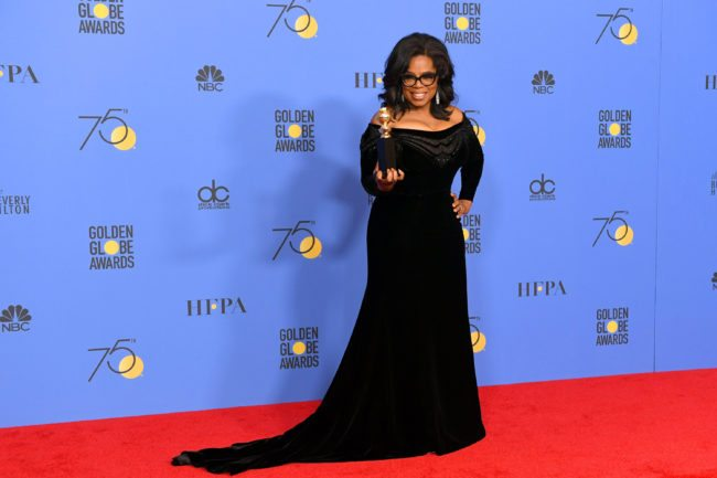 Oprah Winfrey poses with the Cecil B. DeMille Award (Photo by Kevin Winter/Getty Images)