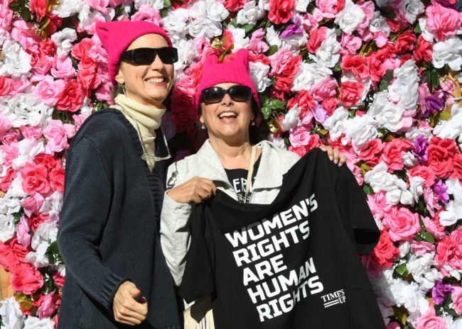 """Protesters, part of a 500,000 strong crowd, attend the Women's Rally on the one-year anniversary of the first Women's March in Los Angeles, California on January 20, 2018. Protestors took to the streets en masse across the United States Saturday, hoisting anti-Donald Trump placards, banging drums and donning pink hats for a second Women's March opposing the president -- one year to the day of his inauguration. Hundreds of thousands of marchers assembled in Washington, New York, Chicago, Denver, Boston, Los Angeles and other cities nationwide, many donning the famous pink knit """"pussy hats"""" -- a reference to Trump's videotaped boasts of his license to grope women without repercussions. / AFP PHOTO / Mark RALSTON (Photo credit should read MARK RALSTON/AFP/Getty Images)"""