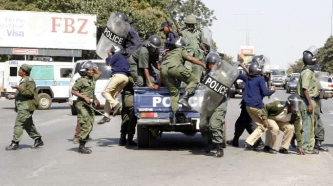 Zambian police officers arrive at the University of Zambia where students protest against the government's removal of fuel and mealie meal subsidies on May 17, 2013 in Lusaka. Zambian President Michael Sata ordered police to arrest and expel the students who were protesting. In a country with high unemployment, 60 percent of people living in poverty and the average income at $3.45 a day, any significant increase will cause economic and social shocks. AFP PHOTO / STRINGER (Photo credit should read STR/AFP/Getty Images)