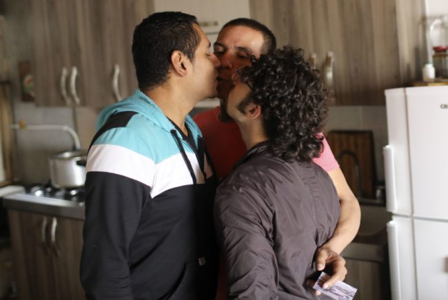 """Manuel Bermudez (L), Alejandro Rodriguez (C) and Victor Prada give each other a kiss at their home in Medellin, Colombia on June 17, 2017. The three men have gained legal recognition as the first """"polyamorous family"""" in the country , where same-sex marriages were legalized last year. / AFP PHOTO / JOAQUIN SARMIENTO (Photo credit should read JOAQUIN SARMIENTO/AFP/Getty Images)"""