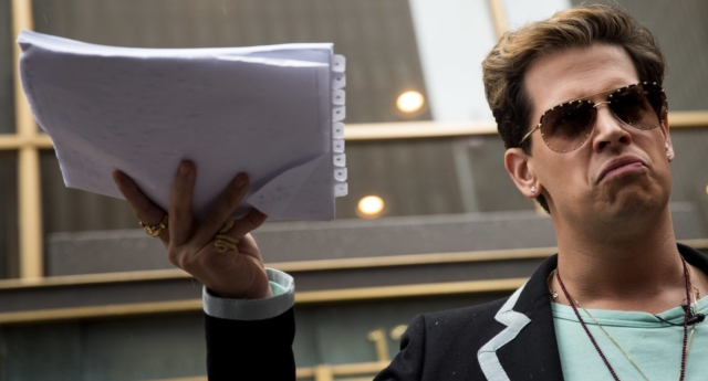 Milo Yiannopoulos holds up a copy of a legal complaint (Photo by Drew Angerer/Getty Images)