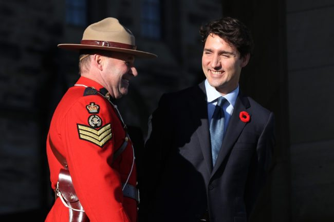 Canadian Prime Minister Justin Trudeau speaks with an RCMP officer before the arrival of the Colombian President Juan Manuel Santos Calderon on Parliament Hill in Ottawa, Ontario, October 30, 2017. / AFP PHOTO / Lars Hagberg (Photo credit should read LARS HAGBERG/AFP/Getty Images)
