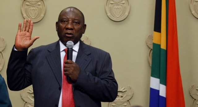 South Africa's new president Cyril Ramaphosa holds up his right hand as he is sworn into office  after being elected by the Members of Parliament at the Parliament in Cape Town, on February 15, 2018. (Photo by MIKE HUTCHINGS/AFP/Getty Images)