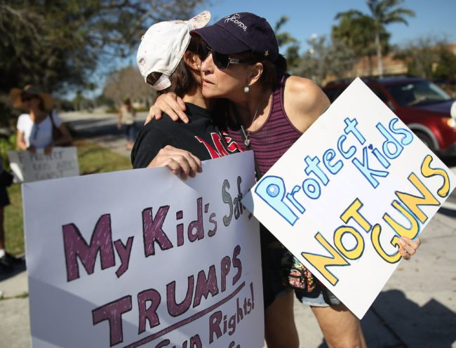 PARKLAND, FL - FEBRUARY 17:  Debby Stout (L) whose daughter was in the Marjory Stoneman Douglas High School when 17 people were killed is hugged by Lori Feldman during a protest against guns on February 17, 2018 in Parkland, Florida. Earlier this week former student Nikolas Cruz opened fire with a AR-15 rifle at the Marjory Stoneman Douglas High School killing 17 people.  (Photo by Joe Raedle/Getty Images,)