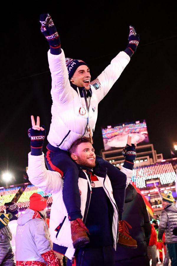 TOPSHOT - US athletes Adam Rippon and Gus Kenworthy parade with other delegations during the closing ceremony of the Pyeongchang 2018 Winter Olympic Games at the Pyeongchang Stadium on February 25, 2018. / AFP PHOTO / Jonathan NACKSTRAND        (Photo credit should read JONATHAN NACKSTRAND/AFP/Getty Images)