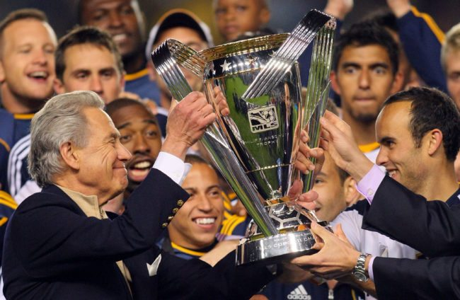 CARSON, CA - NOVEMBER 20:  Landon Donovan #10 of the Los Angeles Galaxy (R) receives the Philip F. Anschutz Trophy from Philip F. Anschutz on the podium after the Los Angeles Galaxy defeated the Houston Dynamo in the 2011 MLS Cup at The Home Depot Center on November 20, 2011 in Carson, California. The Galaxy defeated the Dynamo 1-0 to win the 2011 MLS Cup.  (Photo by Victor Decolongon/Getty Images)
