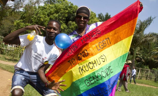 """Ugandan men hold a rainbow flag reading """"Join hands to end LGBTI (Lesbian Gay Bi Trans Intersex - called Kuchu in Uganda) genocide"""" as they celebrate on August 9, 2014 during the annual gay pride in Entebbe, Uganda. Uganda's attorney general has filed an appeal against the constitutional court's decision to overturn tough new anti-gay laws, his deputy said on August 9. Branded draconian and """"abominable"""" by rights groups but popular domestically, the six-month old law which ruled that homosexuals would be jailed for life was scrapped on a technicality by the constitutional court on August 1. AFP PHOTO/ ISAAC KASAMANI        (Photo credit should read ISAAC KASAMANI/AFP/Getty Images)"""