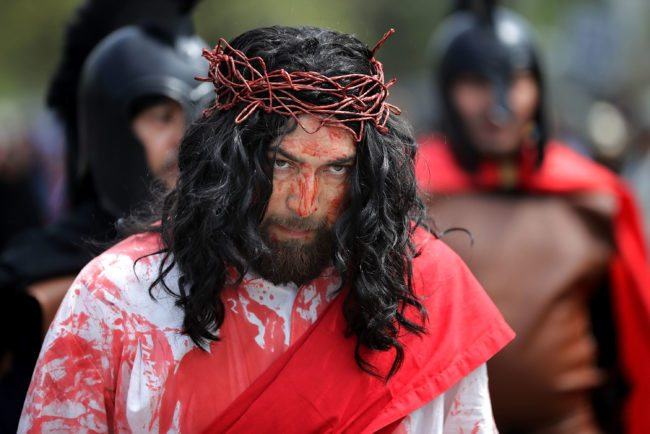 LANGLEY PARK, MD - APRIL 14: Surrounded by observers and actors playing Roman soldiers, Henry Colindres (C) portrays Jesus during a traditional Via Crucis, or Way of the Cross, procession on the Christian Good Friday holiday April 14, 2017 in Langley Park, Maryland. The recreation of the crucifixion of Jesus drew several thousand area Catholics and marched its way through several Maryland neighborhoods in the suburbs of the nation's capital. (Photo by Chip Somodevilla/Getty Images)