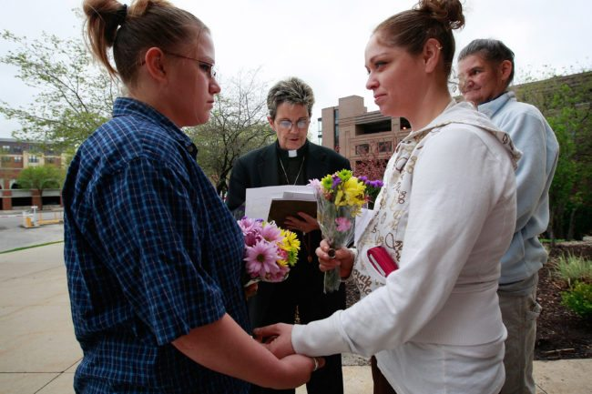 DES MOINES, IA - APRIL 27: Jodie Vandermark-Martinez (R) is married to her partner Jessica during a ceremony performed by Rev. Peg Esperanza (C) on the steps of the Polk County Administration Building April 27, 2009 in Des Moines, Iowa. Today was the first day gay couples were allowed to marry in the state following an April 3, 2009 ruling by the Iowa Supreme Court which declared a legislative ban on same-sex marriage unconstitutional. (Photo by Scott Olson/Getty Images)