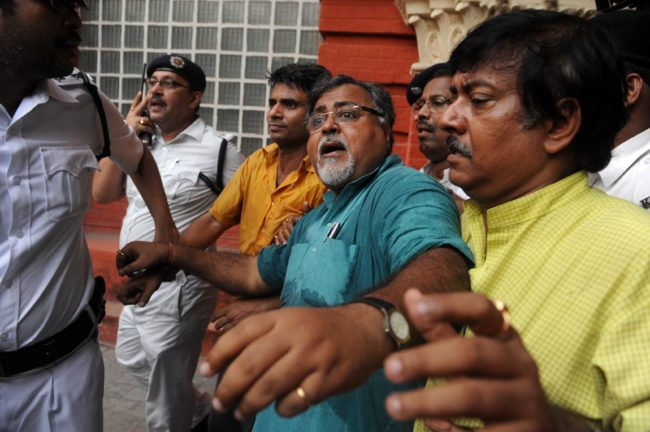 India's Trinamool Congress Party leader Partha Chatterjee (C) reacts as he is escorted out of the Writers Building, the state administrative headquarters, after arrested by police in Kolkata on October 16, 2009. Chatterjee, who is the opposition leader in the West Bengal state assembly, staged a demonstration in front Chief Minister Buddhadev Bhaterjee's office demanding the chief minister's arrest for the alleged arrest of innocent people. AFP PHOTO/Deshakalyan CHOWDHURY (Photo credit should read DESHAKALYAN CHOWDHURY/AFP/Getty Images)