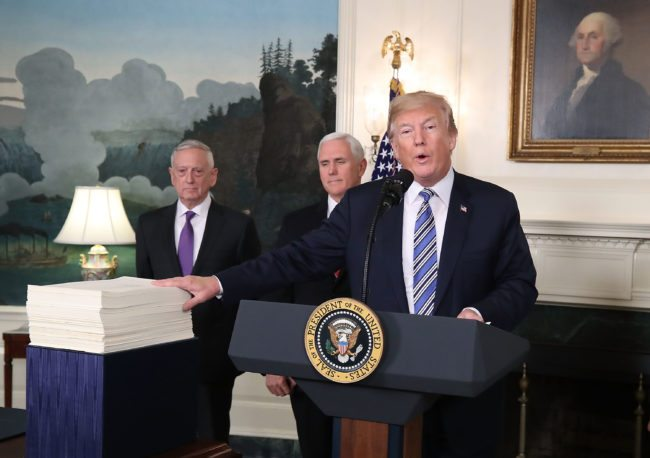 WASHINGTON, DC - MARCH 23: U.S. President Donald Trump gestures to the $1.3 trillion spending bill passed by Congress early Friday, with Vice President Mike Pence (C), and Defense Secretary Jim Mattis (L), in the Diplomatic Room of the White House on March 23, 2018 in Washington, DC. After threatening to veto the legislation earlier today, President Trump announced he had signed the bill, avoiding a government shutdown. (Photo by Mark Wilson/Getty Images)