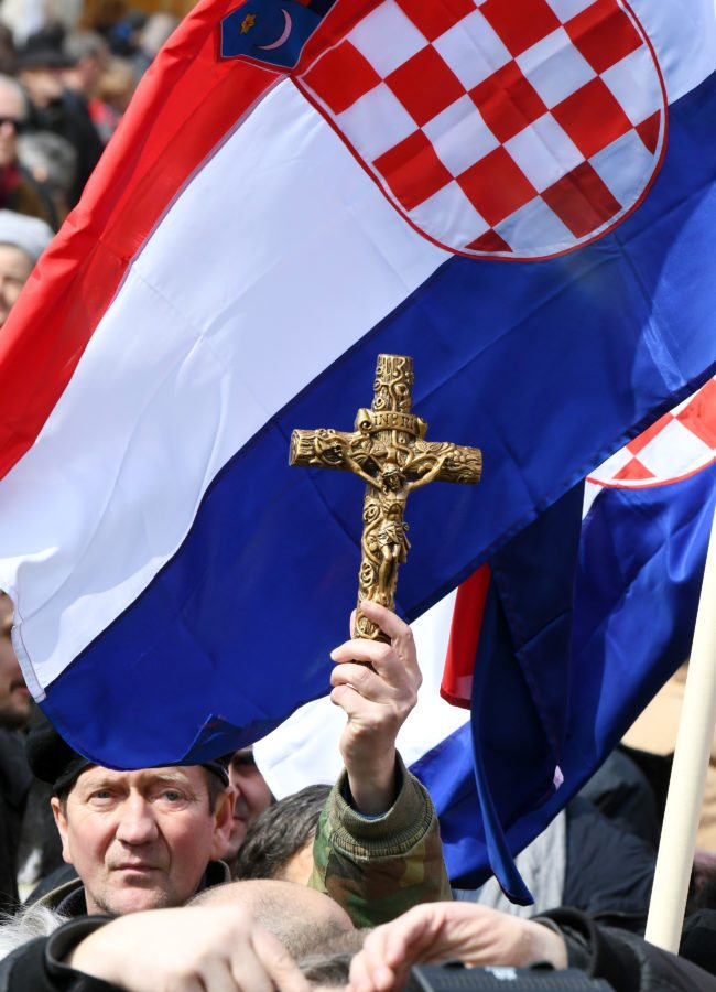 "A man holds a cross as opponents to a treaty safeguarding women, backed by the Roman Catholic Church, protest against its ratification arguing it is imposing what they call a ""gender ideology"" in the Croatian capital, Zagreb, on March 24, 2018. Protestors against the Council of Europe convention on preventing and combating violence against women and domestic violence (Istanbul Convention) -- the world's first binding instrument to prevent and combat violence, from marital rape to female genital mutilation -- hold banners against its ratification, an issue that has split the Balkan country. / AFP PHOTO / STR (Photo credit should read STR/AFP/Getty Images)"