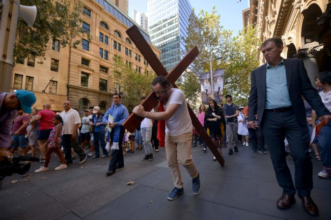 24-year-old student Alec Green, depicting himself as Jesus Christ, carries a cross in a re-enactment from the Bible on Good Friday in Sydney on March 30, 2018. Good Friday, part of the Easter weekend, is a Christian religious holiday commemorating the crucifixion of Jesus Christ and his death and is a public holiday throughout Australia. / AFP PHOTO / Peter PARKS (Photo credit should read PETER PARKS/AFP/Getty Images)