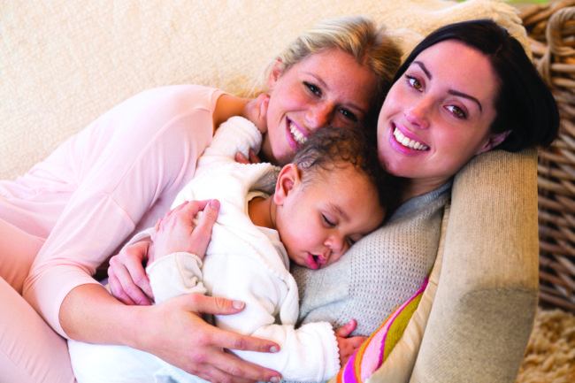 Same sex female couple lying down with their baby son