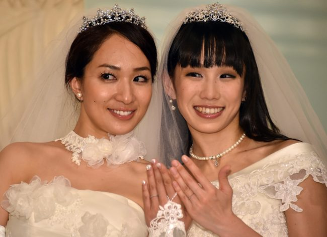 Japanese actress Akane Sugimori (R) and her partner Ayaka Ichinose, both dressed in white, display their wedding rings at a press conference after their marriage ceremony in Tokyo on April 19, 2015. The lesbian couple held a symbolic wedding ceremony in Tokyo, as calls grow for Japan to legalise same-sex marriage. While their marriage will not be recognised under law, actresses Ichinose, 34, and Sugimori, 28 tied the knot in front of some 80 relatives and friends. AFP PHOTO / Yoshikazu TSUNO (Photo credit should read YOSHIKAZU TSUNO/AFP/Getty Images)