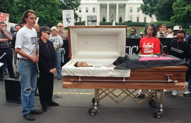 WASHINGTON, UNITED STATES: Aids activists participate in a protest march by opening the casket of AIDS activist Steve Michael as his partner Wayne Turner (L) and his mother Barbara Michael (2nd-L) look on in front of the White House in Washington, DC 04 June 1998. The protesters mourned the death of Michael, the Act Up Washington, DC founder, who died as a result from AIDS 25 May. The group denounced US President Bill Clinton's campaign promises to find a cure for the disease. AFP PHOTO/Jamal A. WILSON (Photo credit should read JAMAL A. WILSON/AFP/Getty Images)