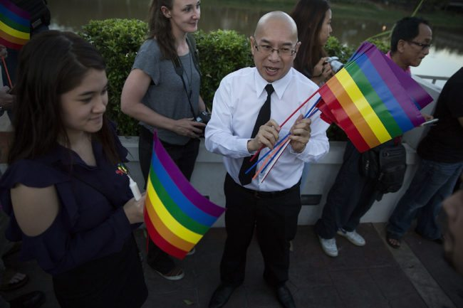 CHIANG MAI, THAILAND - JUNE 14: A man hands out gay pride flags during a candlelight vigil outside the United States Consulate on June 14, 2016 in Chiang Mai, Thailand. 49 people were killed after a gunman opened fire on people in a gay nightclub in Orlando. It was the deadliest mass shooting in U.S. history. (Photo by Taylor Weidman/Getty Images)