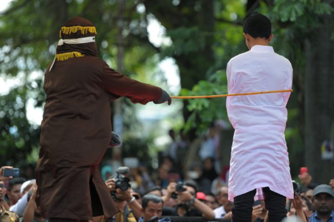 A religious officer canes an Acehnese man (R) 100 times for having sex outside marriage, which is against sharia law, in Banda Aceh on November 28, 2016. Aceh is the only province in the world's most populous Muslim-majority country that imposes sharia law. People can face floggings for a range of offences -- from gambling, to drinking alcohol, to gay sex. / AFP / Chaideer MAHYUDDIN (CHAIDEER MAHYUDDIN/AFP/Getty Images)