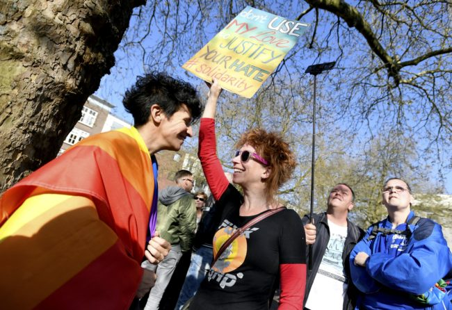 """A woman holds a placard reading """"Don't use my love to justify your hate #solidarity"""" during the Hand in Hand for Diversity, a demonstration against anti-LGBT violence triggered after a gay couple was beaten up, on April 8, 2017 in Arnhem. / AFP PHOTO / ANP / Piroschka van de Wouw / Netherlands OUT (Photo credit should read PIROSCHKA VAN DE WOUW/AFP/Getty Images)"""