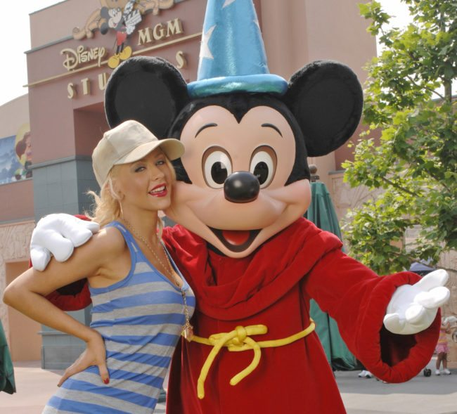 """LAKE BUENA VISTA, FLORIDA - MAY 3: In this handout image provided by Disney, grammy Award-winning artist Christina Aguilera poses with Mickey Mouse at the Disney-MGM Studios on May 3, 2007 in Lake Buena Vista, Fla. It was a """"homecoming"""" for Aguilera, who taped the Disney Channel's """"The New Mickey Mouse Club"""" series at the Disney-MGM Studios as a child star in the early 1990s. (Photo by Diana Zalucky/Disney via Getty Images)"""