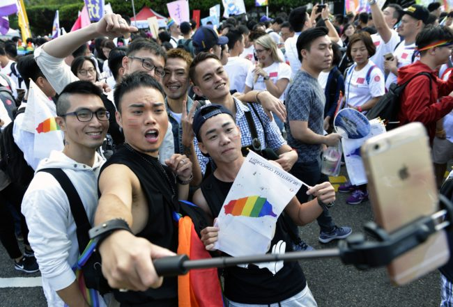 Supporters of same-sex rights take selfies during a gay pride parade in Taipei on October 28, 2017.   Downtown Taipei was a sea of rainbow flags and glitzy costumes on October 28 as tens of thousands marched in Asia's largest gay pride parade, the first since Taiwan's top court ruled in favour of gay marriage. / AFP PHOTO / SAM YEH        (Photo credit should read SAM YEH/AFP/Getty Images)