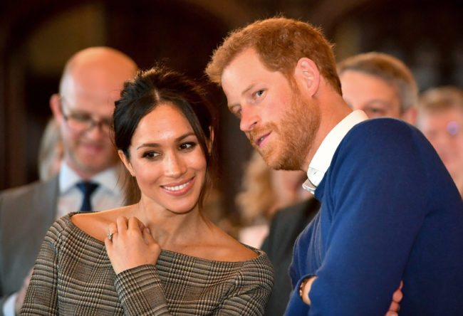 Prince Harry whispers to Meghan Markle as they watch a dance performance by Jukebox Collective in the banqueting hall during a visit to Cardiff Castle on January 18, 2018 in Cardiff, Wales. (Photo by Ben Birchall - WPA Pool / Getty Images)