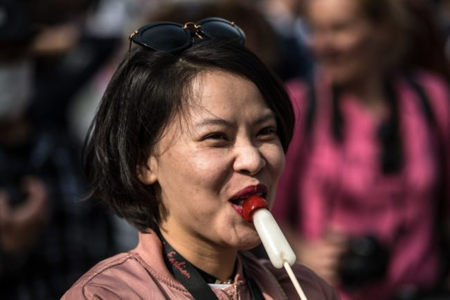 KAWASAKI, JAPAN - APRIL 01: (EDITORS NOTE: Image contains suggestive content.) A woman eats a phallic-shaped lollipop during Kanamara Matsuri (Festival of the Steel Phallus) on April 1, 2018 in Kawasaki, Japan. The Kanamara Festival is held annually on the first Sunday of April. The penis is the central theme of the festival, focused at the local penis-venerating shrine which was once frequented by prostitutes who came to pray for business prosperity and protection against sexually transmitted diseases. Today the festival has become a popular tourist attraction and is used to raise money for HIV awareness and research. (Photo by Carl Court/Getty Images)