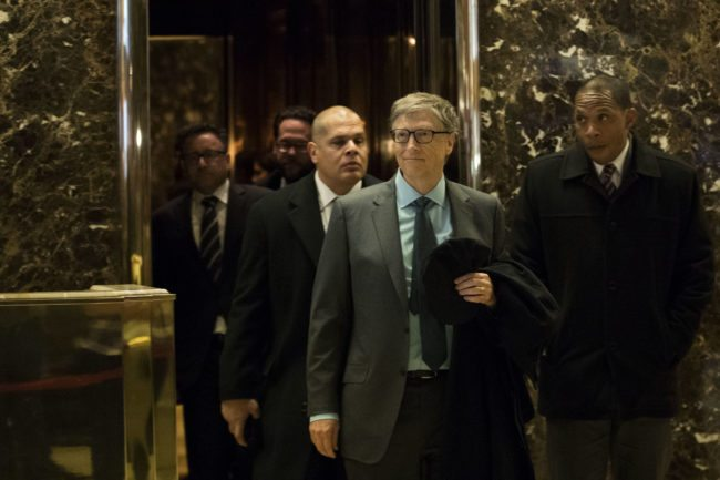 Bill Gates exits an elevator before speaking to reporters at Trump Tower