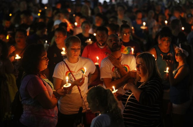 ORLANDO, FL - JUNE 12: People hold candles as they attend a one year anniversary memorial service for victims of the mass shooting at the Pulse gay nightclub being held at Lake Eola Park on June 12, 2017 in Orlando, Florida. Omar Mateen killed 49 people at the club a little after 2 a.m. on June 12, 2016. (Photo by Joe Raedle/Getty Images)