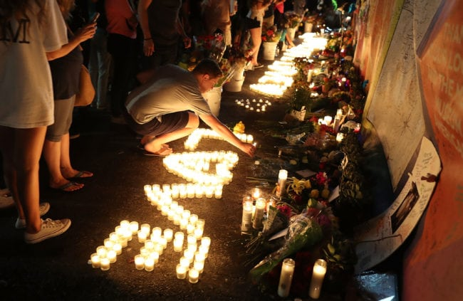 ORLANDO, FL - JUNE 12: Dillon Caldwell places a candle in the memorial setup outside the Pulse gay nightclub as he remembers those lost one year ago during a mass shooting on June 12, 2017 in Orlando, Florida. Omar Mateen killed 49 people at the club a little after 2 a.m. on June 12, 2016. (Photo by Joe Raedle/Getty Images)