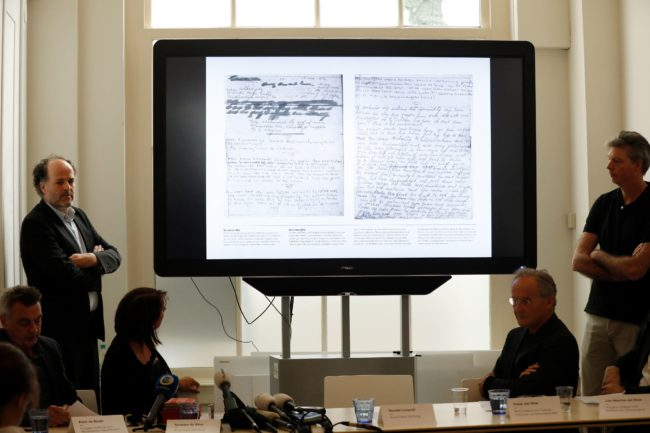 Ronald Leopold (L), executive director of the Anne Frank House, presents two unknown pages of Anne Frank's diary, during a press conference on May 15, 2018 in Amsterdam. - Two pages of Anne Frank's world-famous diary - which she covered over with brown paper, discovering dirty jokes and a teenager's interest in sex - have been made visible with digital photo-editing techniques. (Photo by Bas CZERWINSKI / ANP / AFP) / Netherlands OUT        (Photo credit should read BAS CZERWINSKI/AFP/Getty Images)