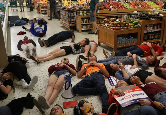 "CORAL SPRINGS, FL - MAY 25: Protesters participate in a ""die'-in"" protest in a Publix supermarket on May 25, 2018 in Coral Springs, Florida. The activists many of whom are Marjory Stoneman Douglas High School students entered the Publix store to protest against the company's support of political candidates endorsed by the National Rifle Association who oppose gun reform. (Photo by Joe Raedle/Getty Images)"