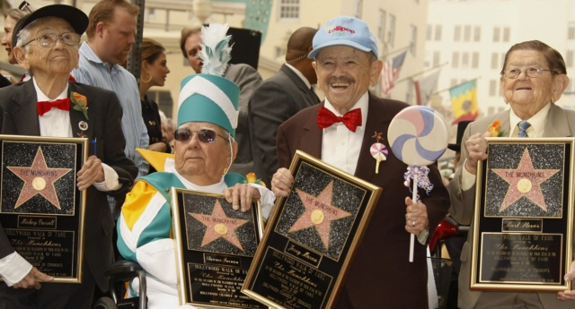 """Jerry Maren (sporting a cap with the words """"the lollipop guild"""") died at the age of 98 (Getty)"""