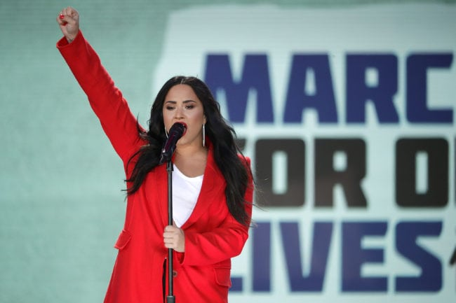 """WASHINGTON, DC - MARCH 24: Demi Lovato performs """"Skyscraper"""" during the March for Our Lives rally on March 24, 2018 in Washington, DC. Hundreds of thousands of demonstrators, including students, teachers and parents gathered in Washington for the anti-gun violence rally organized by survivors of the Marjory Stoneman Douglas High School shooting on February 14 that left 17 dead. More than 800 related events are taking place around the world to call for legislative action to address school safety and gun violence. (Photo by Chip Somodevilla/Getty Images)"""