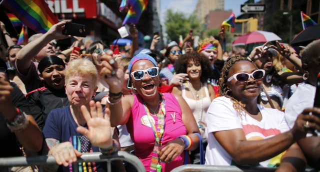 Revellers standing on Seventh Avenue watch the annual Pride Parade on June 24, 2018 in New York City. (Kena Betancur/Getty)