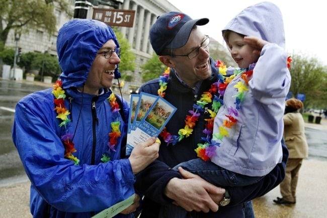 WASHINGTON - APRIL 17:  Doug Metcalfe (L) and his partner Brian Lahmann show their White House Easter Egg Roll event tickets to their daughter, Helen Lahmann-Metcalfe, 4, after picking up the tickets April 17, 2006 in Washington, DC. Members and supporters of Family Pride, a gay and lesbian parents' organization, wore rainbow-colored leis while attending to the 128-year-old event.  (Photo by Chip Somodevilla/Getty Images)