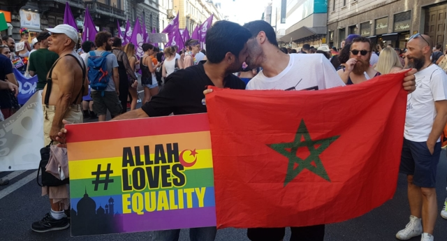 "Wajahat Abbas Kazmi, left, holds a rainbow flag with the slogan ""Allah Loves Equality"" written across it while his friend, right, holds the Moroccan flag as they march through the Milan Gay Pride parade on June 30, 2018 (Photo courtesy of Wajahat Abbas Kazmi)"