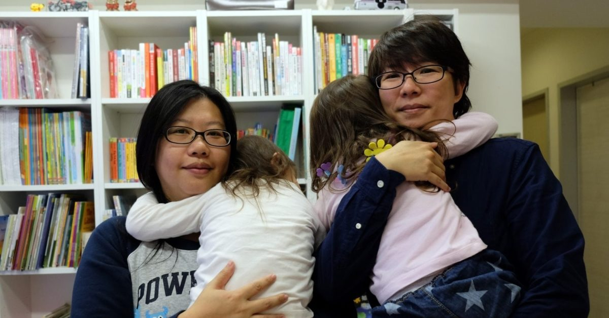 Same-sex parents Hope Chen (L), 37, and Zoro Wen, 34, pose with their twin daughters at their home in Taoyuan, northern Taiwan (Photo by Sam Yeh/ AFP/Getty Images)