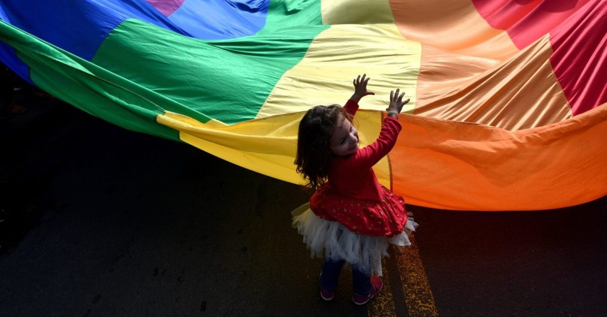A child helps to wave a huge rainbow flag during the Gay Pride parade on September 17, 2017 in Belgrade (Photo by Andrej Isakovic/AFP/Getty Images)