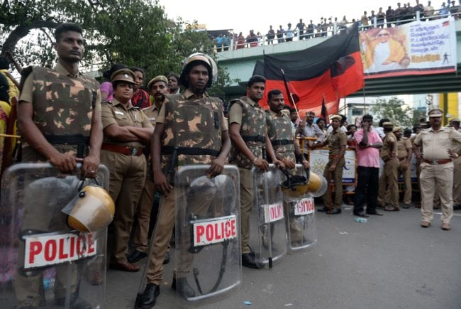 Indian policemen stand guard as supporters of the Dravida Munnetra Kazhagam party gather in front of the hospital where President M. Karunanidhi died, in Chennai on August 7, 2018. - Thousands of people desanded into mourning on August 7 in southern India after the death of revered 94-year-old political leader Muthuvel Karunanidhi. (Photo by ARUN SANKAR / AFP)        (Photo credit should read ARUN SANKAR/AFP/Getty Images)