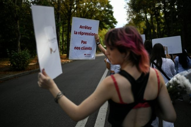 "People hold placards reading ""stop repression, not our clients"", during a march at the Bois de Boulogne in Paris, on August 24, 2018, in tribute to Vanesa Campos, a 36 year-old transsexual sex worker who was killed the week before. (Photo by Lionel BONAVENTURE / AFP)        (Photo credit should read LIONEL BONAVENTURE/AFP/Getty Images)"
