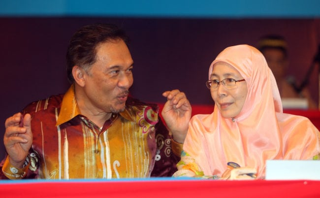 Malaysian opposition leader and former deputy prime minister Anwar Ibrahim (L) and his wife Wan Azizah Wan Ismail (R) President of People's Justice Party, gestures during the People's Justice Party National Congress 2010 in Petaling Jaya, near Kuala Lumpur on November 28, 2010. Malaysian opposition leader Anwar Ibrahim urged his party to close ranks and gear up for national polls, after a bout of bitter party infighting which he admitted has damaged its image. AFP PHOTO/ KAMARUL AKHIR (Photo credit should read KAMARUL AKHIR/AFP/Getty Images)