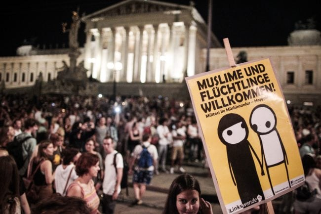 Protesters gather to demonstrate against ill-treatment of migrants after the bodies of 71 refugees were found in an abandoned truck last week in Vienna on August 31, 2015. Around 20,000 people demonstrated police said. The banner reads 'Muslims and refugees welcome'. AFP PHOTO / PATRICK DOMINGO        (Photo credit should read PATRICK DOMINGO/AFP/Getty Images)