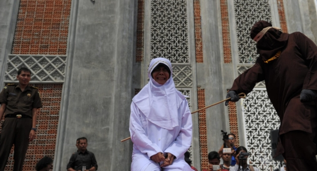 A woman is caned in Aceh, Indonesia, where sharia law is in effect (CHAIDEER MAHYUDDIN/AFP/Getty)