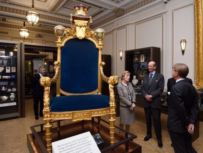 LONDON, ENGLAND - SEPTEMBER 29: Prince Edward, Duke of Kent (C), also the 10th Grand Master of the United Grand Lodge of England, is shown the Grand Master's Chair by Director of the Library and Museum, Diane Clements (L), during a visit to open a gallery titled 'Three Centuries of English Freemasonry' at the Library and Museum of Freemasonry on September 29, 2016 in London, England. To mark Freemasonry's 300th anniversary, a new permanent gallery space is being opened and features items including Winston Churchill's Masonic apron and the Grand Master's Throne. (Photo by Carl Court/Getty Images)