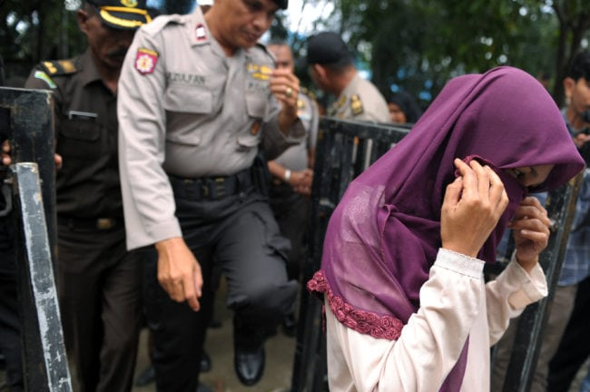An Indonesian woman (R) walks prior to receiving 100 lashes of the cane for having sex outside marriage, which is against Sharia law, in Banda Aceh on November 28, 2016. Aceh is the only province in the world's most populous Muslim-majority country that imposes sharia law. People can face floggings for a range of offences -- from gambling, to drinking alcohol, to gay sex. / AFP / CHAIDEER MAHYUDDIN (Photo credit should read CHAIDEER MAHYUDDIN/AFP/Getty Images)
