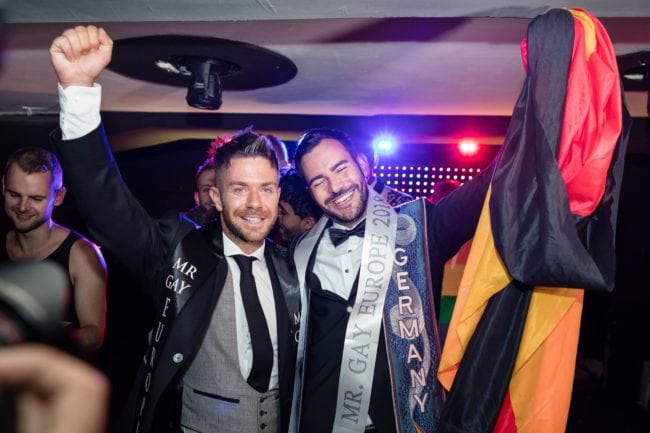 German Enrique Doleschy (R) reacts after he won the Mister Gay Europe 2018 beauty contest as Matt Rood from UK - Mister Gay Europe 2017 stands by in the Haven And Hell club in Poznan, August 11, 2018. (Photo by Wojtek RADWANSKI / AFP) (Photo credit should read WOJTEK RADWANSKI/AFP/Getty Images)
