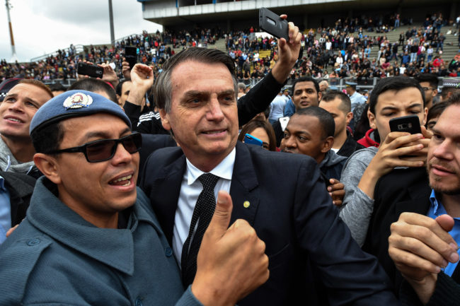 Brazilian presidential candidate for the Social Liberal Party (PSL) Jair Bolsonaro (C) poses for a picture with a military man during the graduation ceremony of a military school in Sao Paulo, Brazil on August 17, 2018. - Brazilian general elections will take place next October 7. (Photo by NELSON ALMEIDA / AFP) (Photo credit should read NELSON ALMEIDA/AFP/Getty Images)